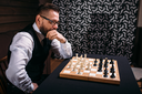 Pensive male chess player in glasses thinking about game strategy. Intelligence competition concept
