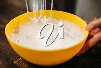 Dough whipping in bowl with a mixer. Sweet cake cooking preparation. Wooden background