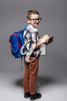 Little child with school bag and book, studio photo shoot. Young pupil with backpack and textbook. Boy with schoolbag