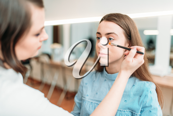 Professional beautician work with woman eyebrows in beauty studio. Cosmetic salon