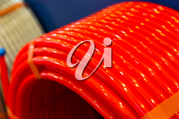 Roll of of red plastic pipe in plumbing shop, pvc. Coil of new water pipeline
