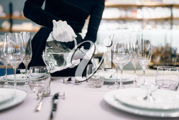 Waitress in gloves pours drinks into glasses, table setting. Serving service, festive dinner decoration