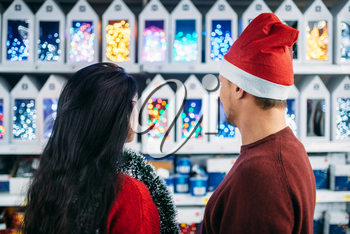 Young couple looks on christmas gifts in supermarket, family tradition. December shopping, choosing of holiday decorations