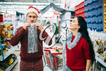 Couple buying christmas costume in supermarket, family tradition. December shopping of new year holiday goods and decorations