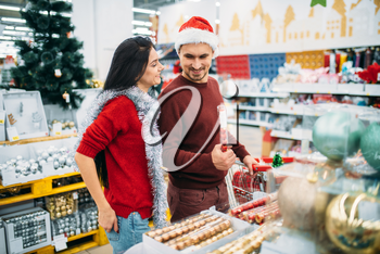 Young couple with cart in department of holiday decorations in supermarket, family tradition. December shopping of new year or christmas goods