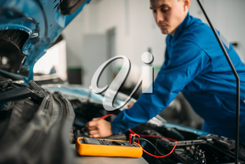 Car repairman with multimeter, battery inspection. Auto-service, vehicle wiring diagnostic, electrician occupation