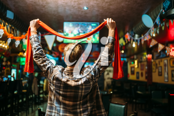 Football fan with scarf raises his hands up and watching the match of the favorite team in sports bar, back view. Tv broadcasting of the game in pub