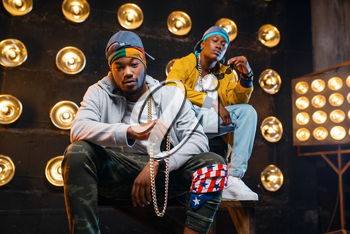 Two black rappers sitting on the steps, perfomance on stage with spotlights on background. Rap performers on scene with lights, underground music, urban style