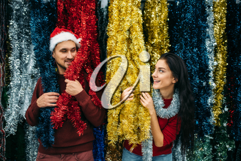 Young couple plays with holiday fluffy garland, purchase of christmas decoration in supermarket, family tradition. December shopping
