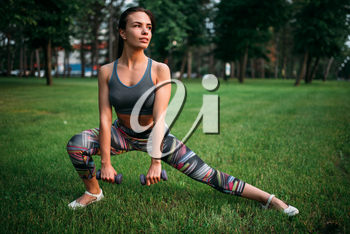 Slim woman exercise with dumbbell in summer park. Sporty girl on outdoors morning workout