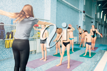 Female instructor and group of children doing exercises near a swimming pool. Healthy and happy childhood concept. Sportive kids activity in modern sport center.
