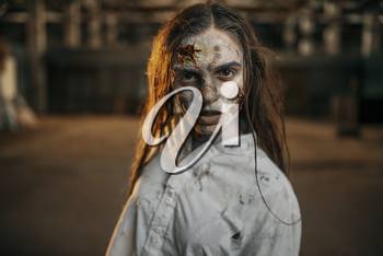 Female zombie walking in abandoned factory, scary place. Horror in city, creepy crawlies attack, doomsday apocalypse, bloody evil monster