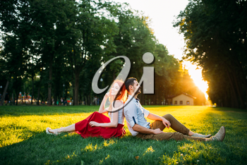 Love couple sits on a grass in summer park. Romantic date of attractive woman and young man