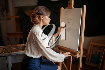 Female painter in studio, pencil sketch on easel. Creative paint, woman drawing portrait, workshop interior on background