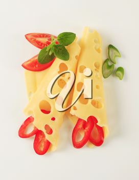 Thin slices of Swiss cheese garnished with vegetables