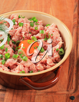 Raw minced meat and egg yolk in a ceramic pot