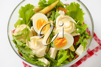bowl of mixed salad with eggs and baby corn - close up