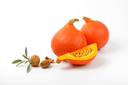 orange pumpkins with walnuts and sprig of sage on white background