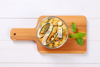 bowl of raw colored pasta on wooden cutting board