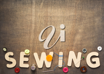sewing tools and letters on wooden table background, top view