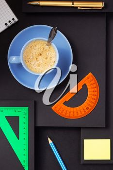 office supplies and cup of coffee at abstract black paper background
