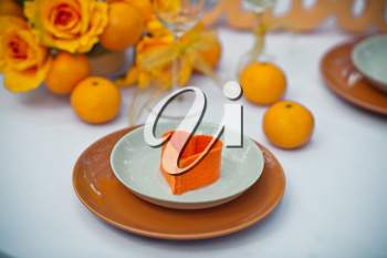 Table with plates and oranges.