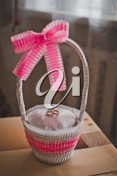 Beautiful basket for wedding gold rings with pink bows.