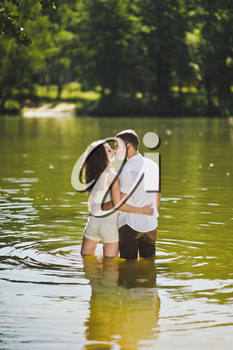 A tender embrace on the shore of the wooded lake.