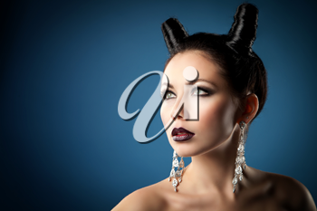 The girl in the image of the demon-tempter and hair in the form of horns. Photo taken in the studio on a background.