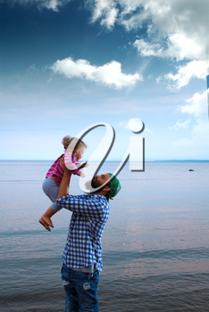 Dad or father and his baby daughter hugging on a boat or ferry in the sea on a cool summer day