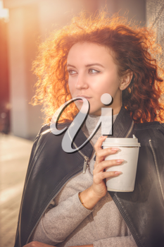 red-haired girl with a glass of coffee is standing by the wall. Portrait at sunset