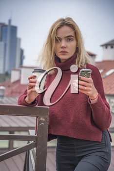 a girl drinks coffee and looks into the phone