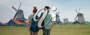 A married couple of tourists travel around the Netherlands.Traditional Dutch windmills with canal near the Amsterdam, Holland