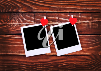 Blank instant photo and red hearts on wooden background