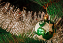 Green Christmas ball with star with tinsel
