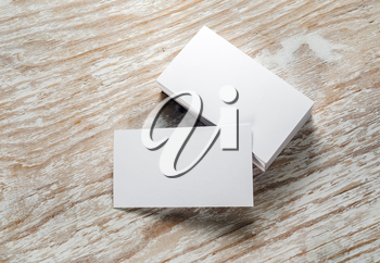 Photo of blank business cards with soft shadows on light wooden background. Mock-up for branding identity.