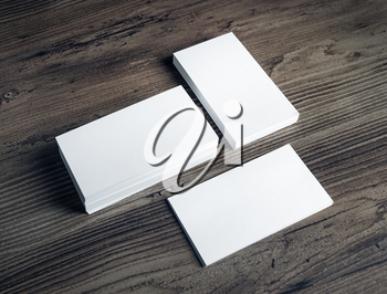 Photo of blank white business cards on vintage wooden table background. Mock up for ID. Blank template for branding identity.