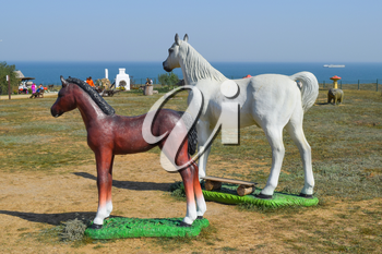White horse and brown foal. Figures of horses made of plastic on the lawn.