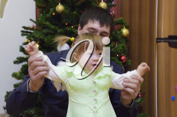 Year-old girl with dad in the background of the Christmas tree. A child with gray eyes and blond hair.