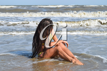 The girl in a yellow bathing suit on the beach. Girl with black hair sitting in sea water head bowed. Beach vacation.