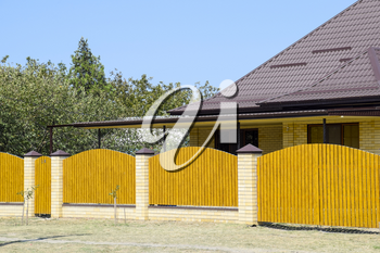 Brick house with corrugated metal profile roof and wooden fence. Beautiful view of the facade. Style of design.
