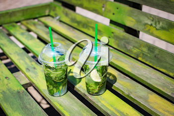 Mojito non-alcoholic in plastic glasses on a wooden green background, summer street festival