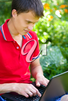 Young man is playing on laptop, outdoor shoot
