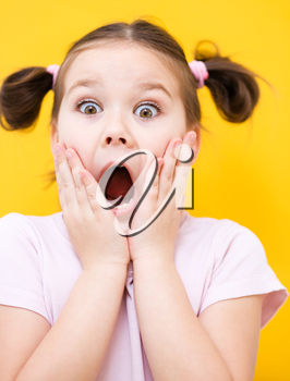 Little girl is holding her face while listening to somebody