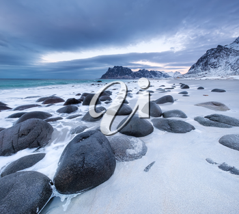 Seashore with stones during sunset. Beautiful natural seascape in the Norway