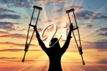 Happy disabled person with raised hands crutches sunset. Concept happy disabled