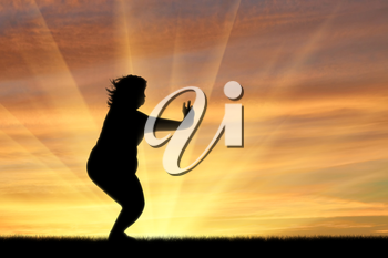 concept of fight against obesity and overweight. Silhouette of a fat woman is doing exercises at sunset