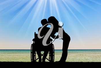 Silhouette of a disabled man in a wheelchair and his wife who is kissing by the sea. The concept of caring and supporting disabled people