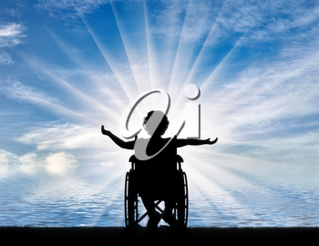Silhouette of a happy disabled child girl sitting in a wheelchair at the seaside. Concept of happy children with disabilities