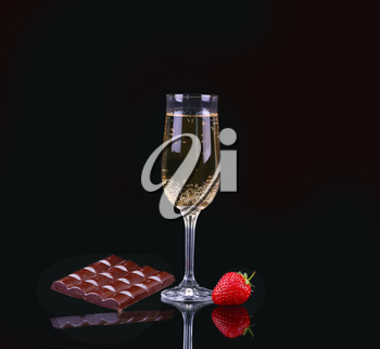 Glass of cold champagne with strawberries on a black background